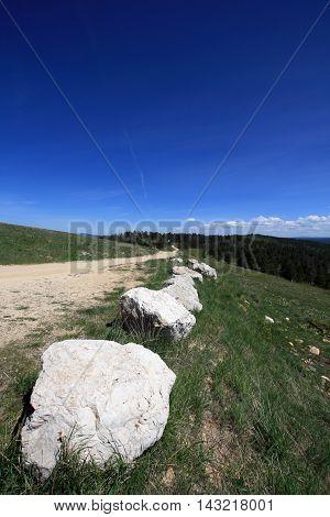 Cement Ridge gravel road with limestone boulder boundary in the Black Hills in South Dakota USA