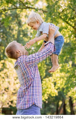Young dad playing with his son in the park by throwing him up.