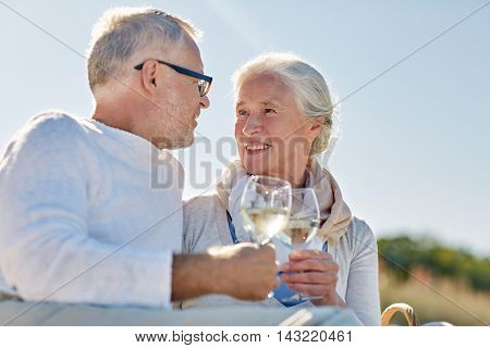 family, age, holidays, leisure and people concept - happy senior couple having picnic and clinking wine glasses on summer beach