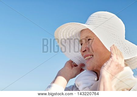 age, leisure and people concept - happy senior woman in sun hat on summer beach