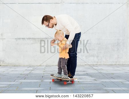 family, childhood, fatherhood, leisure and people concept - happy father teaching little son to ride on skateboard over urban street background