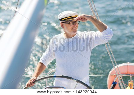 sailing, age, tourism, travel and people concept - happy senior man in captain hat on steering wheel and navigating sail boat or yacht floating in sea poster