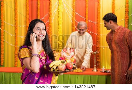 indian young women holding plate full of fruits and talking over cel phone or mobile phone or smartphone in ganpati festival or ganesh utsav