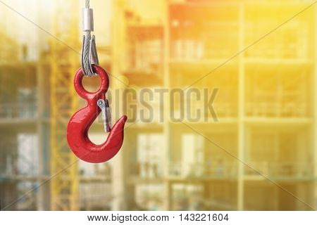 Red lifting crane hook on construction site with lighting effect background.