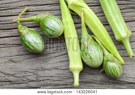 fresh green eggplant and Okra on wooden floor