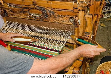 A man seated at a wooden handloom creating a handwoven woollen fabric