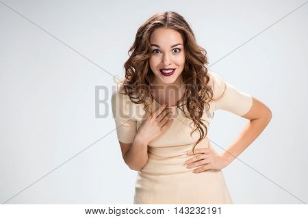Portrait of young woman with shocked facial expression over gray background
