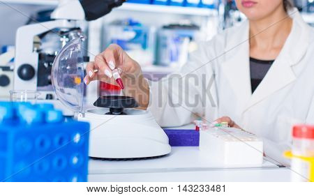 Young woman work with PCR centrifuge in laboratory