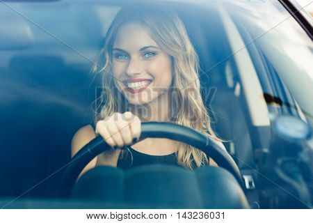 Pretty blond woman with curly hair behind the wheel of car with bright big smile