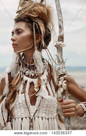 Attractive wild boho woman in white tribal dress portrait