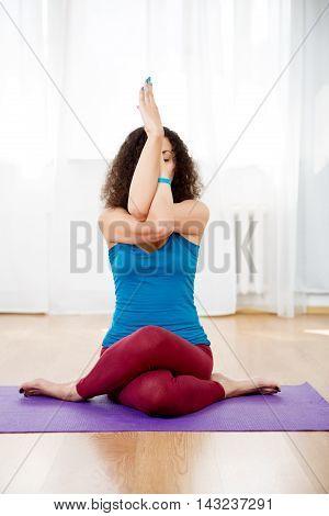 Portrait of young woman sitting in yoga pose mix gomukhasana and garudasana in gym, vertical image