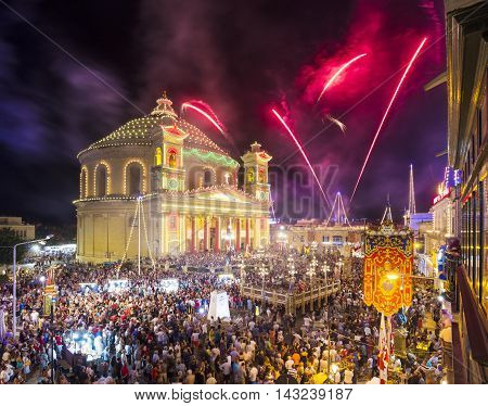 MOSTA MALTA - 15 AUG. 2016: Fireworks at the Mosta festival at night with the famous Mosta Dome and the People of Malta are celebrating the Feast of the Assumption also known as the feast of 'Santa Maria'.