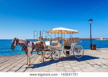Horse carriage for transporting tourists in old port of Chania on Crete Greece