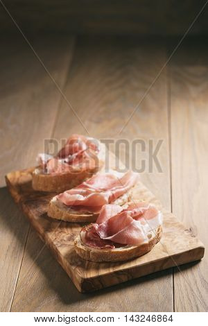 simple ciabatta slices with speck ham on wood table