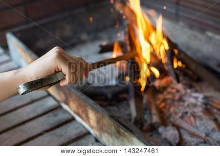 Starting Fire for Charcoal Grill. Arm With Long-Handled Tongs Setting Fire Closeup. Bright Flames and Burning Wood. Get Your Grill On. Fire Preparation for Barbecue.