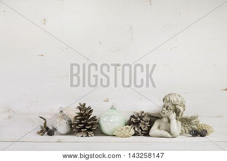 Vintage and nostalgic christmas decoration with angel on wooden white shabby chic background.
