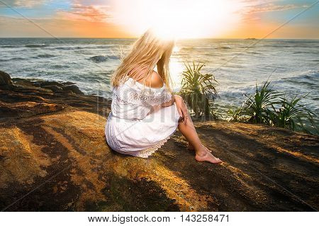 Woman sitting in the white dress on the rock in the rays of setting sun with her head in flare. Wide angle shot photo with double light exposition.