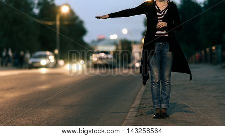 young woman tries to catch a car on night road