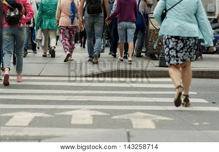 legs of people on a pedestrian crossing on a cloudy day