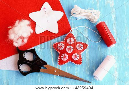 Felt Christmas star decor, paper pattern pinned to red felt sheet, scissors, thread, needle, cord on blue wooden background. Christmas background. Winter craft project for children and beginners