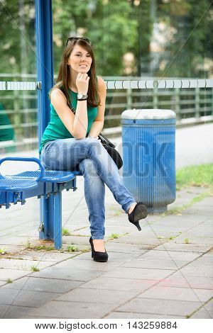 young brunette woman sitting at bus station and smiles