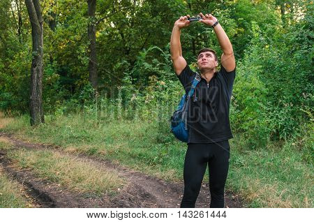 Portrait Of A Man Traveller Searching Connection On The Phone In The Forest.