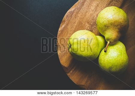 Three green pear on wooden cutting board on a black background. Low key scene top view