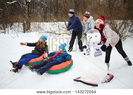 Three adults let go down from hill two children on snowtubes at winter