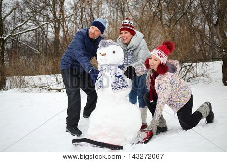 Three adults pushing down snowman from hill at winter, focus on snowman