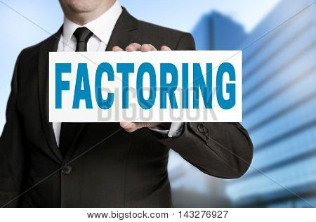 factoring sign is held by businessman background
