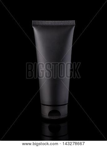 Black cosmetic tube isolated on black background