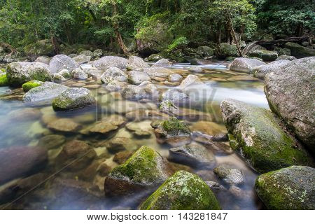 Water of the Mossman River flows over ancient rocks and boulders in Mossman Gorge, Queensland, Australia