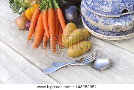 vegetables for potage on a white table with bowl and tablespoon