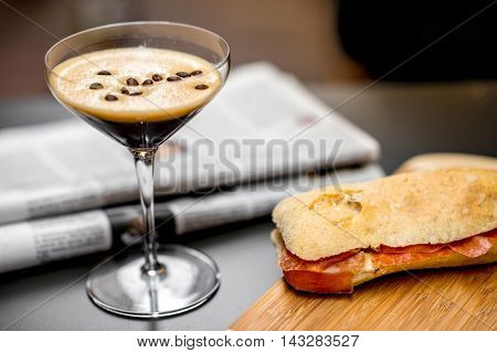 Shakerato drink in cocktail glass with panini and newspaper on the table. Italian lunch with traditional coffee and sandwich with prosciutto