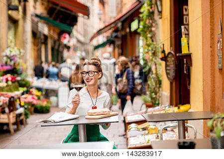 Young woman sitting at the cafe with shakerato coffee and panini outdoor on the famous street with local food markets in Bologna city.