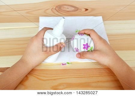 Child holds a decoupage Easter egg and glue. Child doing a beautiful Easter egg. Step