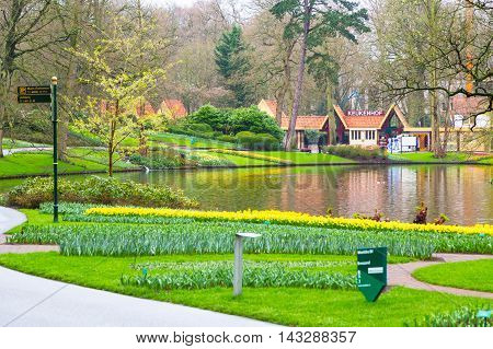 Lisse, Netherlands - April 4, 2016: Park entrance and flowerbed with yellow daffodil flowers blooming in flower spring garden, Netherlands