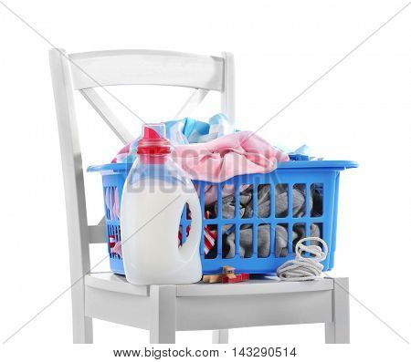 Blue plastic basket with baby laundry and cleanser on white background