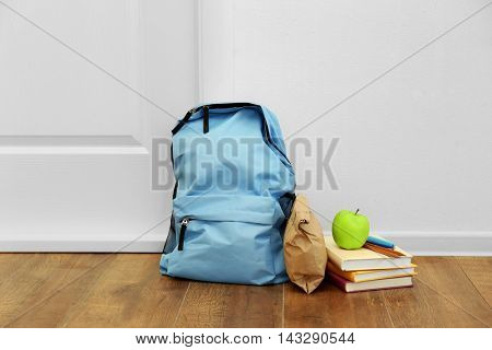 Schoolbag with lunch near door