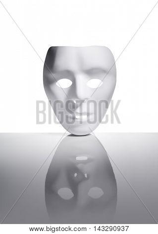 White plastic mask on reflective surface.