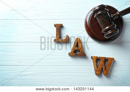 Word law with judges gavel on wooden background