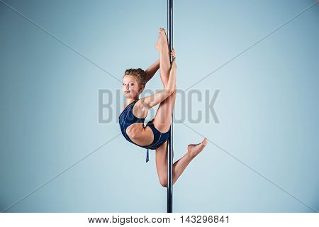 The strong and graceful sports young girl performing acrobatic exercises on pylon on blue background poster