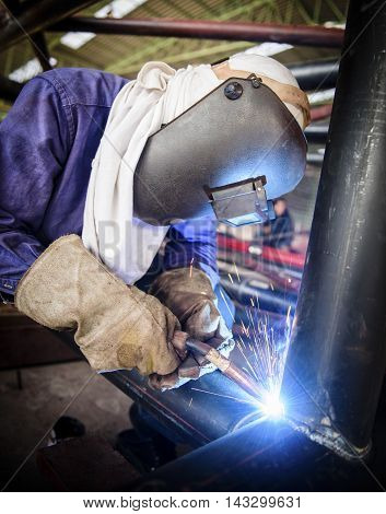 Industrial workers cutting and welding metal with many sharp sparks, Welder working a welding metal with protective mask and sparks.