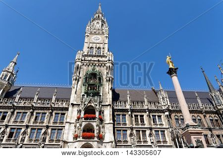 The golden sculpture of Saint Mary and the New Town Hall at Marienplatz Munich main square Germany.
