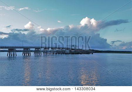 Bridge in Beaufort over water under cloudy sky.