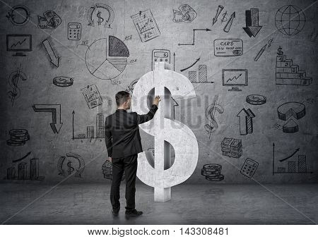Back view of a businessman touching big concrete dollar sign on the backgound of business doodles. Economy and finance. Money and profit. Successful lifestyle.