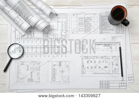 Top view of a draftsman's workplace with a plan, a magnifier, a pencil, a mug of coffee and rolled drafts. Creative workspace. Engineering plan. Architecture and draftmanship.