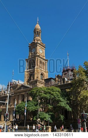 SYDNEY, AUSTRALIA - APRIL, 2016 : People walking in front of Sydney Town Hall with clock tower in Sydney, Australia on April 21, 2016. Designed by Tasmanian architect J.H. Willson