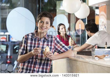 Happy Boy Having Ice Cream At Parlor