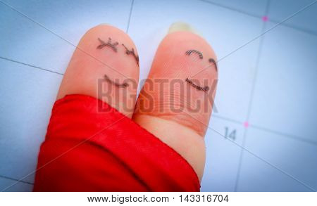 Abstract vintage tone of finger writing face of man and woman holding together smiling on calendar and marking on number 14 with love sign, valentine concept.